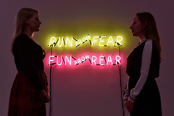 "© Licensed to London News Pictures. 31/07/2017. London, UK. Gallery staff in front of a neon work called ""Run From Fear, Fun From Rear"", 1972, by Bruce Nauman.  Preview of the new Artist Rooms exhibition of Bruce Nauman at Tate Modern on currently until July 2018.  Nauman is widely regarded as one of the most innovative and influential American artists working today.  The Artist Rooms gallery is the London hub for showcasing work from the Artist Rooms collection which is owned jointly by Tate and the National Galleries of Scotland.  Photo credit : Stephen Chung/LNP"