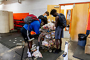Members of the North Dallas Bulldogs Football team pick food bags to take home after the first day of practice during the Covid-19 pandemic. The school has a large population of students living under the poverty line and a sizable number of the students are homeless. The situation has worsened since many come from food insecure homes even before the onset of the pandemic. The schoo is located in one of Dallas' most affluent areas of the city.<br />.(Photo by Jaime R. Carrero)