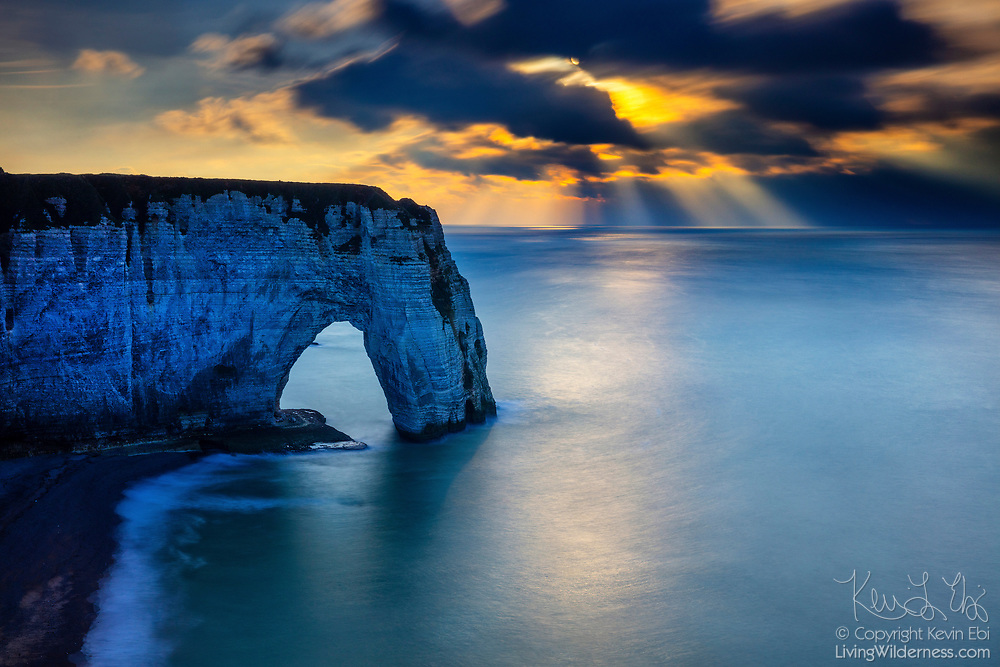 Crepuscular Rays, also known as god beams, form over the Atlantic Ocean and a large sea arch called Manneporte in the late afternoon in Étretat, France. Manneporte is the largest of the three natural sea arches that have formed in the white chalk cliffs, known as the Falaise d'Étretat, which are as tall as 90 meters (300 feet).