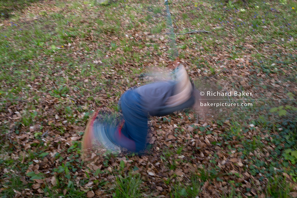 A blurred 7 year-old boy plays on a swing in local woods, on 23rd April 2017, in Wrington, North Somerset, England.