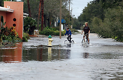 October 7, 2016 - New Smyrna Beach, FL, USA - Bicyclists make their way through a flooded street as heavy rains from Hurricane Matthew cause flooding Thursday, Oct. 7, 2016 in New Smyrna Beach, Fla., as the Category 4 storm brushed the Florida east coast. (Credit Image: © Red Huber/TNS via ZUMA Wire)