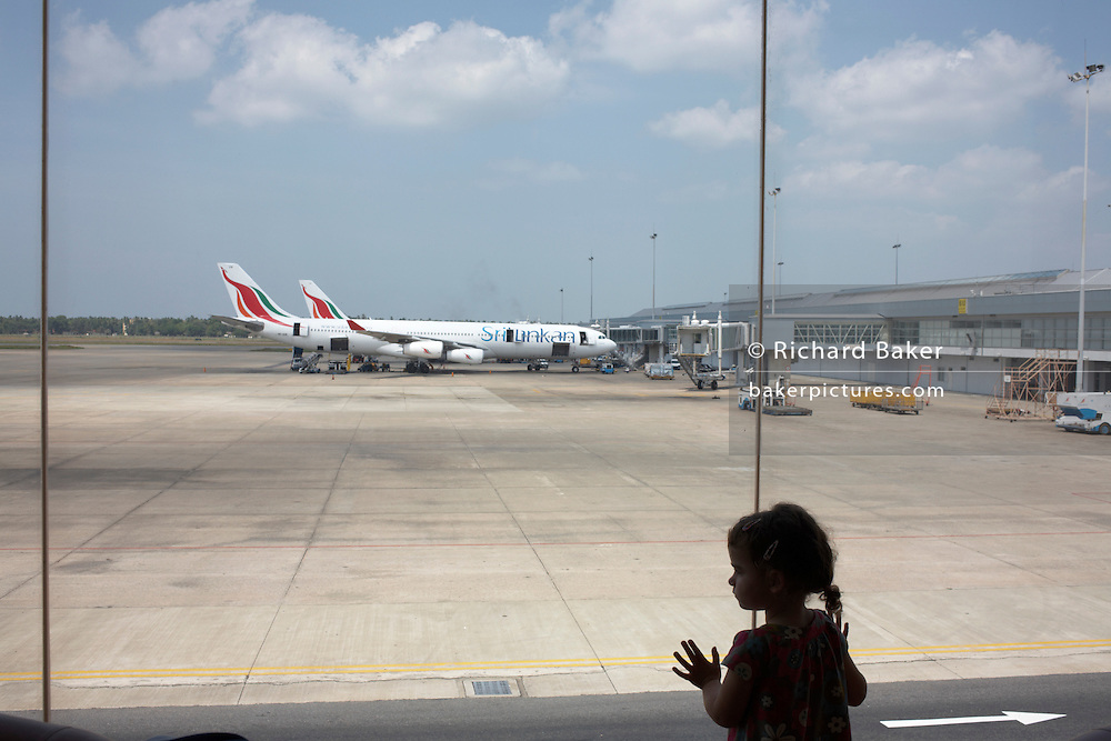 A young girl in transit at Colombo Airport, gazes from a window across the apron where Sri Lankan Airbuses are sitting.