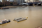 Boats on River Thames with rubbish collection pontoon in foreground, London view to the South Bank and part of Blackfriars bridge.