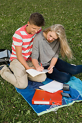 Teenage couple doing homework in park