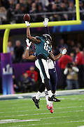 Philadelphia Eagles wide receiver Torrey Smith (82) leaps in the air while trying to catch a deep pass broken up by New England Patriots cornerback Eric Rowe (25) during the 2018 NFL Super Bowl LII football game against the New England Patriots on Sunday, Feb. 4, 2018 in Minneapolis. The Eagles won the game 41-33. (©Paul Anthony Spinelli)
