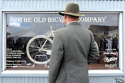 © Licensed to London News Pictures. 17/09/2011. GOODWOOD, UK. A man looks in the window of 'The old Bicycle Company'. The Goodwood Revival at Goodwood in West Sussex today (17 September 2011). The revival is the world's largest historic motor race meeting, which relieves the 'glorious' days of the race circuit. Competitors and enthusiasts all dress in period fashion to enhance the experience. Photo credit : Stephen Simpson/LNP