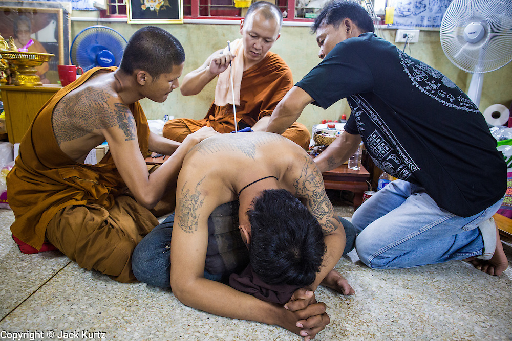 "22 MARCH 2013 - NAKHON CHAI SI, NAKHON PATHOM, THAILAND: A man gets a sacred Sak Yant tattoo at Wat Bang Phra during the tattoo festival. Wat Bang Phra is the best known ""Sak Yant"" tattoo temple in Thailand. It's located in Nakhon Pathom province, about 40 miles from Bangkok. The tattoos are given with hollow stainless steel needles and are thought to possess magical powers of protection. The tattoos, which are given by Buddhist monks, are popular with soldiers, policeman and gangsters, people who generally live in harm's way. The tattoo must be activated to remain powerful and the annual Wai Khru Ceremony (tattoo festival) at the temple draws thousands of devotees who come to the temple to activate or renew the tattoos. People go into trance like states and then assume the personality of their tattoo, so people with tiger tattoos assume the personality of a tiger, people with monkey tattoos take on the personality of a monkey and so on. In recent years the tattoo festival has become popular with tourists who make the trip to Nakorn Pathom province to see a side of ""exotic"" Thailand. The 2013 tattoo festival was on March 23.    PHOTO BY JACK KURTZ"
