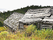 An 1890s house collapses in ruin. American frontier architecture is preserved at Elkhorn State Park, Montana, USA. The silver, gold and lead mines at Elkhorn began booming in 1875, then declined in 1892 as silver prices dropped. A few miners still work the Elkhorn mines and live in private homes nearby, within Beaverhead-Deerlodge National Forest.  Directions: I-15 at Boulder exit, 7 miles south on Montana 69, then 11 miles north on county graveled road.  (Lat 46.275,  Lng  -111.946)