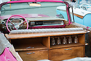 A cabinet with wine glasses has been added to the back of a pink vintage convertible in Havana, Cuba, ready to drive tourists around the city.
