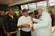 """This handout photo from KFC shows Colonel Sanders look-alike Bob Thompson serving a free two-piece Kentucky Grilled Chicken meal to Milton Scheser Tuesday, Sept. 29, 2009 at a Louisville, Ky., KFC restaurant that has been converted into a """"World Hunger Relief Kitchen"""" during the lunch rush to feed residents of the local Wayside Christian Mission. KFCs across the country will be collecting donations for World Hunger Relief now through the end of October. (Photo by Brian Bohannon)"""