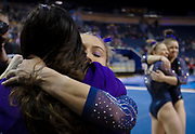 """Olivia Karas of the Michigan Wolverines hugs assistant coach Maile'Ana Kanewa-Hermelyn after competing in the floor exercise against Nebraska in their """"Flip for Chip"""" meet while Abby Heiskell and Natalie Wojcik hug at Crisler Center on February 3, 2019 in Ann Arbor, Michigan."""