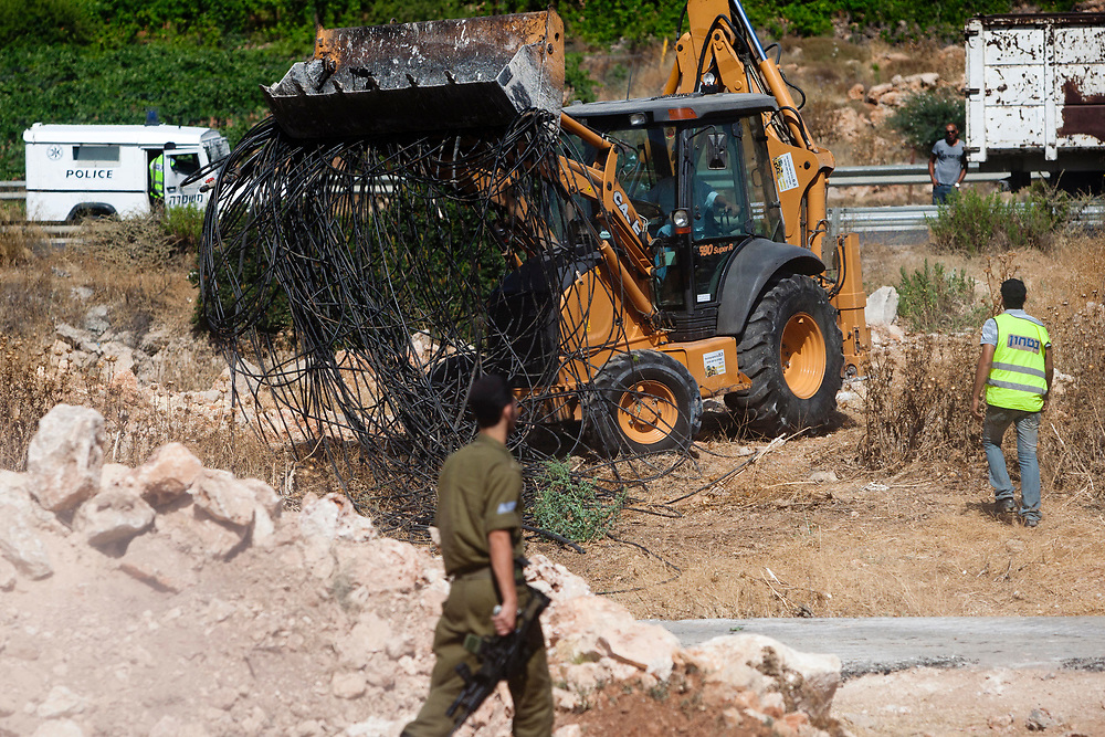 A construction vehicle gatheres confiscated water pipes intended for illegally rerouting water, from a Palestinian farm near the West Bank city of Hebron on 14 July 2010.