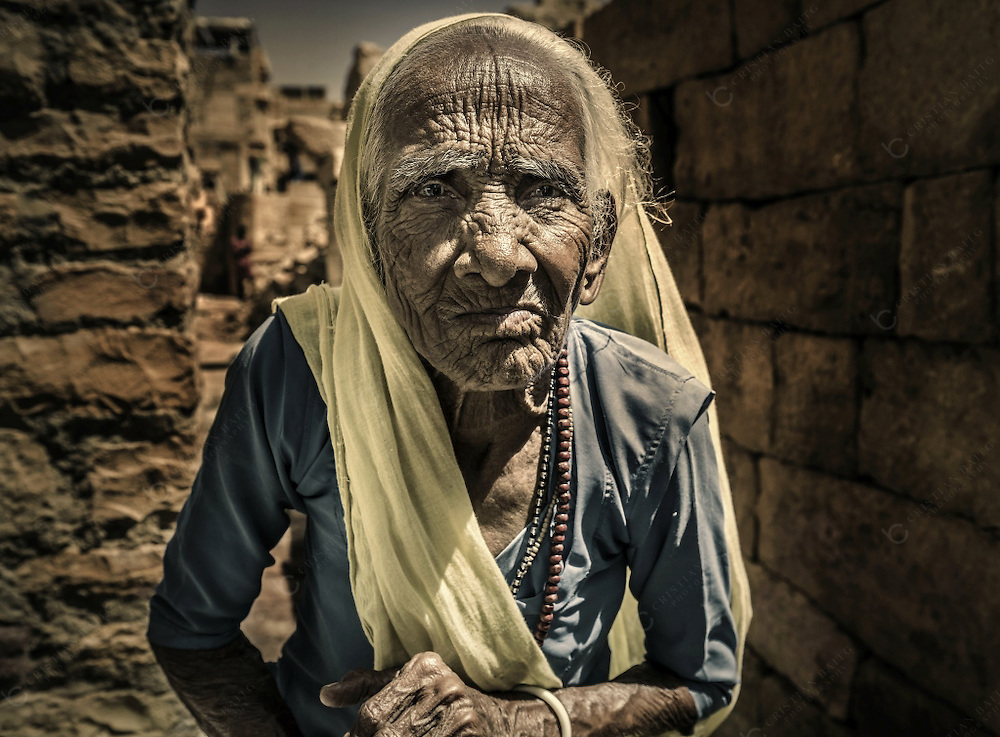 Old woman inside the fort of Jaisalmer Rajasthan India. It is the only fort left in Rajasthan were people still live inside the walls of the fortification. Built in 1156 by the Bhati Rajput ruler Jaisal, Jaisalmer Fort with massive sandstone walls are an important tourist attraction.