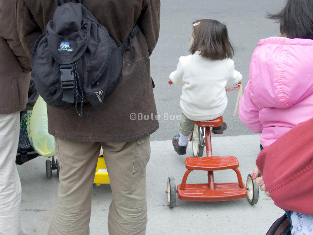 parents with there children waiting before crossing the street