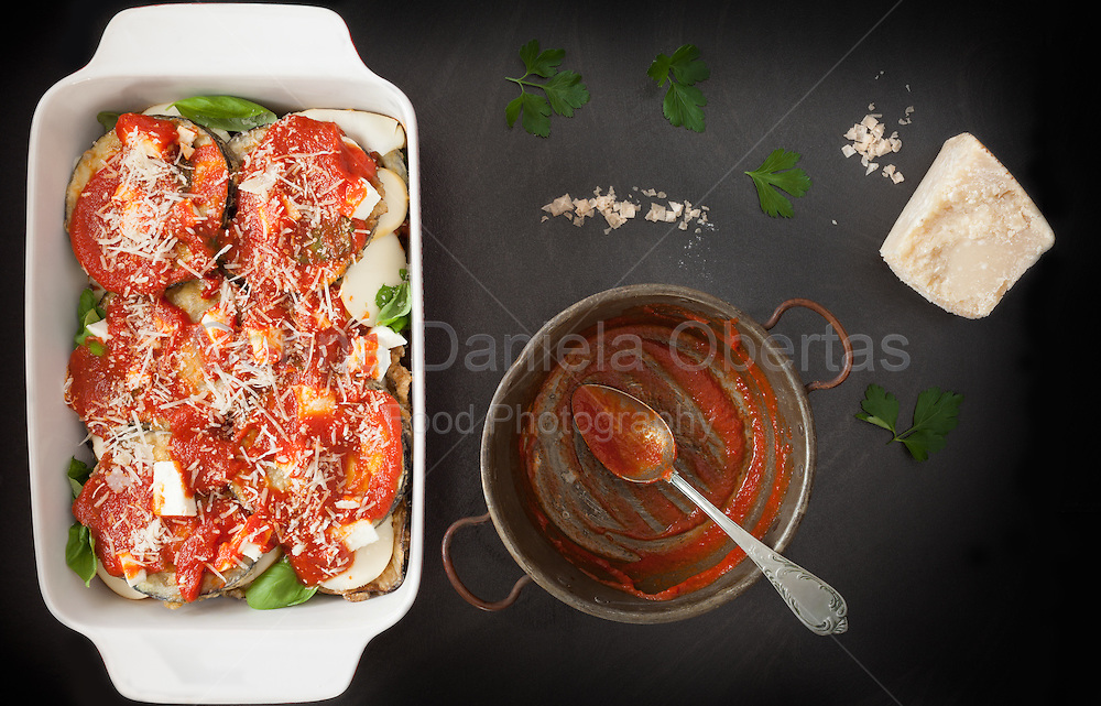 Preparing eggplant parmigiana, last step, top with fried eggplant slices, tomato sauce and grated parmesan cheese.