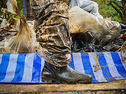 30 JULY 2013 - KOH SAMET, RAYONG, THAILAND:  A worker's oil covered boot on Ao Prao beach on Koh Samet island. About 50,000 liters of crude oil poured out of a pipeline in the Gulf of Thailand over the weekend authorities said. The oil made landfall on the white sand beaches of Ao Prao, on Koh Samet, a popular tourists destination in Rayong province about 2.5 hours southeast of Bangkok. Workers from PTT Global, owner of the pipeline, and up to 500 Thai military personnel are cleaning up the beaches. Tourists staying near the spill, which fouled Ao Prao beach, were evacuated to hotels on the east side of the island, which was not impacted by the spill. PTT Global Chemical Pcl is part of state-controlled PTT Pcl, Thailand's biggest energy firm.     PHOTO BY JACK KURTZ