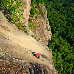 """A man climbs """"Top of the Prow"""" on Cathedral Ledge.  Echo Lake State Park in North Conway, New Hampshire.  White Mountains."""