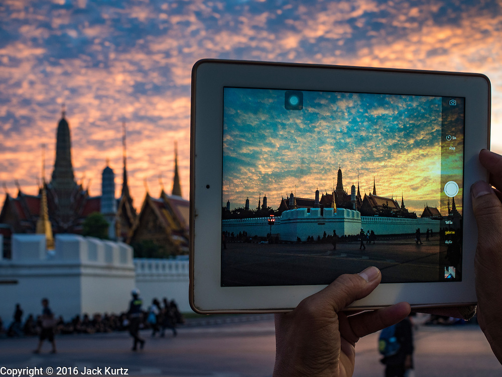 05 NOVEMBER 2016 - BANGKOK, THAILAND:  A man takes a picture of the Grand Palace with his iPad. Crowd of mourners continue to go to the palace to honor the King, nearly three weeks after his death. Thais are honoring their late King, Bhumibol Adulyadej, also known as Rama IX, in various ways. Many barbers are offering mourners free haircuts on the streets near the Grand Palace, where the King is lying in state and communities around the palace are offering free meals to mourners walking to the palace.    PHOTO BY JACK KURTZ