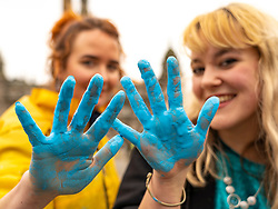 Glasgow, Scotland, UK. 21 March, 2019. A  'Blue Wave' demonstration by the Extinction Rebellion climate change protest group saw protesters make blue footprints, made from water-soluble paint, across George Square to the City Chambers. The peaceful protest briefly held up traffic. The Group aims to highlight threat of rising water levels in the River Clyde and of global climate change. L to R activists Emrys and Cheyenne after the Blue Wave protest.