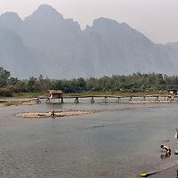 Two men washing in the river water of Nam Song River.