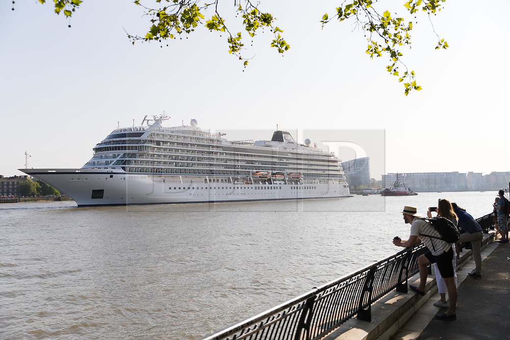 © Licensed to London News Pictures. 06/05/2018. London, UK. People watch as 228-metre-long cruise ship Viking Sun is seen making her way down the River Thames at the end of a 3 day visit to Greenwich in south east London. The visit by Viking Sun, which has a capacity of 930 passengers, marks the beginning of London's cruise ship season. For passengers on board, London was the end of a 141 night round the world cruise which started in Miami last December. Photo credit: Vickie Flores/LNP