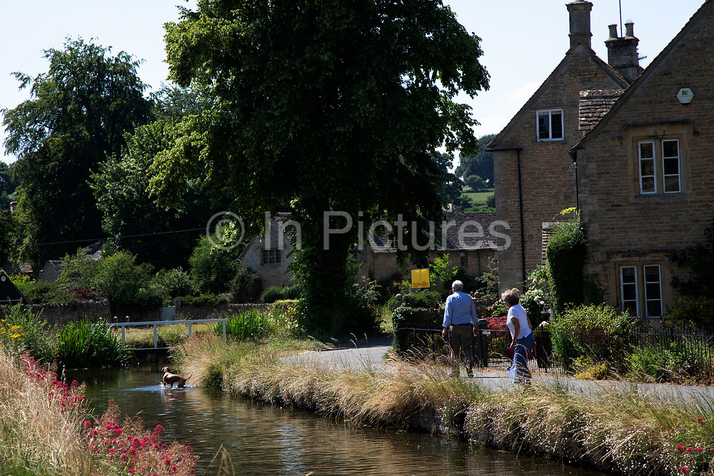 Lower Slaughter in The Cotswolds, United Kingdom. Lower Slaughter village is built on both banks of the River Eye, a slow-moving stream, crossed by two footbridges. Most of the 16th and 17th century homes in the village use Cotswold stone. The name of the village derives form the Old English term 'slough' meaning 'wet land'. The Cotswolds is an area in south central England. The area is defined by the bedrock of limestone that is quarried for the golden coloured Cotswold stone. It contains unique features derived from the use of this mineral; the predominantly rural landscape contains stone-built villages and historical towns.