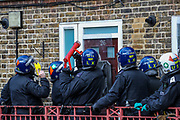 Meanwhile, police are breaking the door of a suspected fugitive another officer is standing by with a taser fearing that the man who is alleged to have assaulted members of the public and emergency worker in south London on  Tuesday, Aug 18, 2020, would come out and attack them before he surrenders. <br /> Members of the MET police crew stormed into his barricaded doorstep after Martin wouldn't respond to their multiple calls to surrender as he was declared that he was going to be arrested.<br /> After breaking the door police stumbled into a barricade made of a ladder, washing machine, several chairs and other wood and plastic items. After forcing themselves into his apartment, police couldn't find him. The search is on-going. (VXP Photo/ Vudi Xhymshiti)