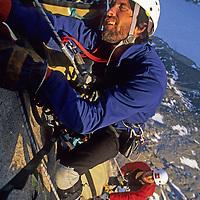 BAFFIN ISLAND, NUNAVUT, CANADA. Mark Synnott, exhausted by hauling huge bags up Great Sail Peak. Jared Ogden helps.  Stewart Valley below. (MR)