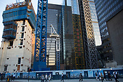 Construction site for The Pinnacle in the City of London, UK. Lift shafts, finished buildings , cranes and steel all rise behind a hoarding.