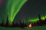 Alaska , Brooks Range. Iniakuk Lake Lodge. Northern Lights over a lit cabin in the Brooks Range at Iniakuk Lake Lodge.