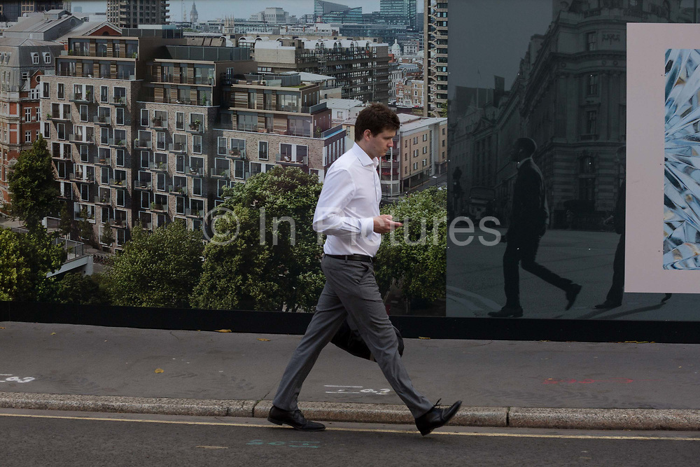 A pedestrian walks past a construction hoarding for the new luxury apartment development called The Denizen, a controversial 10-storey building by Taylor Wimpey that locals say will dominate their view and block their daylight, on 30th October 2017, in London, England. Residents from Bowater House on the Golden Lane Estate have erected banners by artists Jeremy Deller and Elizabeth Price to picket the developers. Despite this, Wimpey say, We are one of the UKs largest residential developers. As a responsible developer we are committed to working with local people and communities.