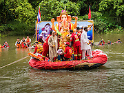 31 AUGUST 2014 - SARIKA, NAKHON NAYOK, THAILAND: A statue of Ganesh is submerged during the Ganesh Festival at Shri Utthayan Ganesha Temple in Sarika, Nakhon Nayok. Ganesh Chaturthi, also known as Vinayaka Chaturthi, is a Hindu festival dedicated to Lord Ganesh. It is a 10-day festival marking the birthday of Ganesh, who is widely worshiped for his auspicious beginnings. Ganesh is the patron of arts and sciences, the deity of intellect and wisdom -- identified by his elephant head. The holiday is celebrated for 10 days, in 2014, most Hindu temples will submerge their Ganesh shrines and deities on September 7. Wat Utthaya Ganesh in Nakhon Nayok province, is a Buddhist temple that venerates Ganesh, who is popular with Thai Buddhists. The temple draws both Buddhists and Hindus and celebrates the Ganesh holiday a week ahead of most other places.    PHOTO BY JACK KURTZ