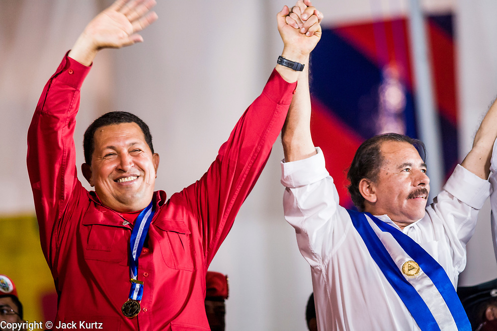 """10 JANUARY 2007 - MANAGUA, NICARAGUA: HUGO CHAVEZ, President of Venezuela, left, and DANIEL ORTEGA, President of Nicaragua, wave to the crowd during Ortega's inaugural speech in Managua.  Daniel Ortega, the leader of the Sandanista Front, was sworn in as the President of Nicaragua Wednesday. Ortega and the Sandanistas ruled Nicaragua from their victory of """"Tacho"""" Somoza in 1979 until their defeat by Violetta Chamorro in the 1990 election.  Photo by Jack Kurtz"""