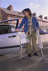 Teenage girl with physical disability closing door after getting out of car,