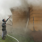Bill Ward uses a garden hose to assist firefighters in putting out a fire as multiple engines responded to a house fire along Virginia Avenue in the Longacre neighborhood of Smithers on Sunday morning, October 21, 2018. Ward, who lives down the street, mentioned that the person living at the home came down the street yelling, and everyone grabbed what they could to put out the fire until emergency personnel arrived. No injuries were initially reported and the cause of the fire remained unknown at the scene.
