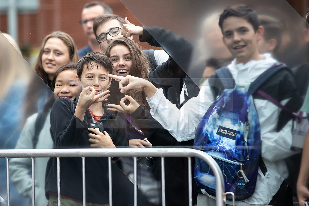 """© Licensed to London News Pictures. 27/07/2019. Manchester, UK. A crowd of onlookers , including some gesturing with their fingers in an """"O"""" shape - historically meaning OK and recently adopted by some to indicate white supremacy - gather to catch a glimpse of British Prime Minister Boris Johnson leaving the Science and Industry Museum after a speech in Manchester City Centre . Johnson was due to re-announce the HS3 rail link between Manchester and Leeds . Photo credit: Joel Goodman/LNP"""