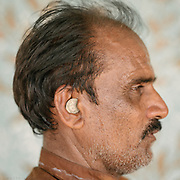 At a pilgrim road stall, a waiter keeps 5 rupees change handy in his ear.