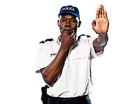 """Portrait of an Afro American police officer holding a hand up to motion """"stop"""" while blowing whistle on white background"""