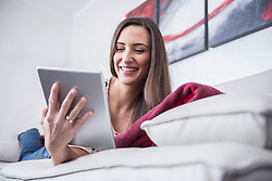 Beautiful woman lying on couch and using a digital tablet, Munich, Bavaria, Germany