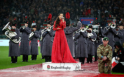Laura Wright signs the national anthem in the rain before the game