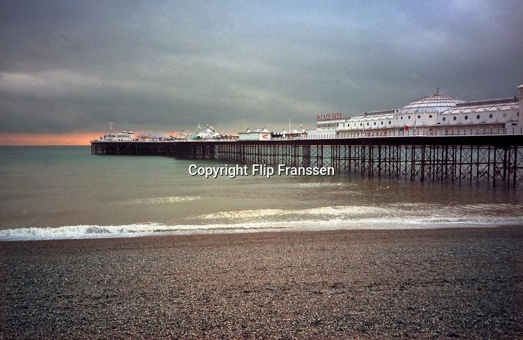 Engeland, Brighton, 5-10-1997Wandelen langs het strand bij de pier bij een donkere avondlucht en ondergaande zon . Toerisme,toeristisch,toeristische,brexit,Foto: Flip Franssen