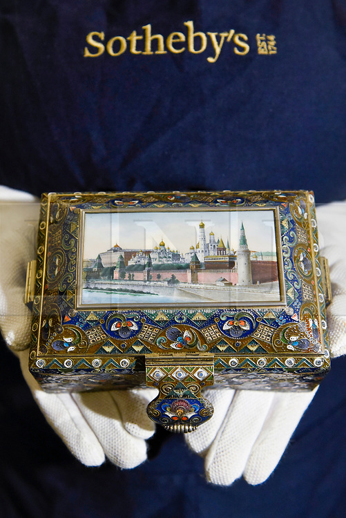 """© Licensed to London News Pictures. 22/11/2019. LONDON, UK. A technician presents """"A silver-gilt, cloisonné and pictorial enamel casket"""", 1908-1917, by Feodor Ruckert (Est. GBP100-150k) at the preview for the upcoming sales of Russian artworks at Sotheby's New Bond Street.  The Russian Pictures and Works of Art, Fabergé and Icons sales take place on 26 November.  Photo credit: Stephen Chung/LNP"""
