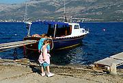 Two children exploring waterfront, Korcula town, island of Korcula, Croatia.