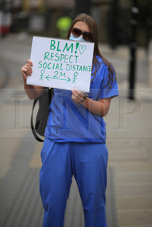 © Licensed to London News Pictures. 07/06/2020. Manchester, UK. A woman wearing medical scrubs holds up a sign asking protesters to respct social distancing guidelines at a Black Lives Matter demonstration ain Manchester City Centre . Ongoing protests have and are being held in Manchester and around the world , after George Floyd was killed whilst being restrained by police in Minneapolis on 25th May 2020 . Photo credit: Joel Goodman/LNP