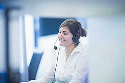 Happy businesswoman wearing headset and working in office, Freiburg Im Breisgau, Baden-Württemberg, Germany