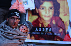 April 14, 2018 - Srinagar, Jammu and Kashmir, India - A Kashmiri man holds a doll as he participates in the protest demanding justice for 8-year old Asifa Bano. Asiifa, the nomadic gujjar child was brutally raped and murdered in Kathua district of Jammu in January 2018. The Crime Branch of Police has filed a charge sheet of the case in a local court and indicted eight people in the case. (Credit Image: © Faisal Khan via ZUMA Wire)