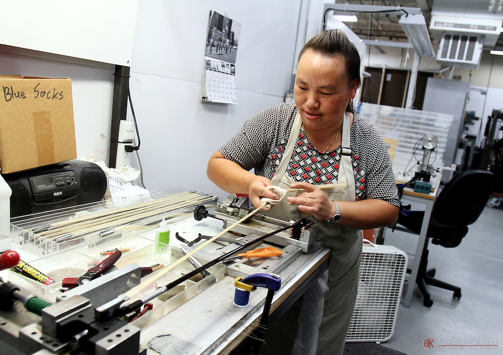 Pang Thao attaches horse hair to a bow made of composite material Tuesday, July 21, 2015, at CodaBow in Winona, Minn. Thao used to work on traditional bows, but says she can do her work much faster with the composite bows.