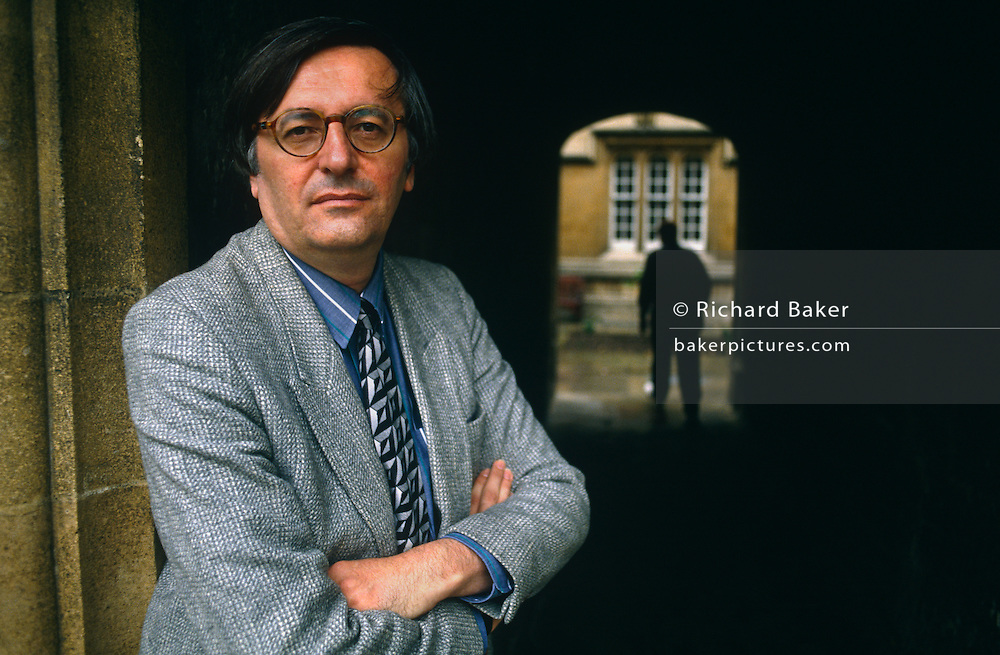 With a shadowy person in the background, John Gray the political scientist, stands with arms folded and wearing a grey jacket and his round-frame glasses in the Quadrangle of Jesus College, Oxford, amid classical architecture. He is a prominent British political philosopher, author and currently School Professor of European Thought at the London School of Economics. Prior to this he was Professor of Politics at Oxford University. He is a former supporter of the New Right and a regular contributor to the Guardian and the Times Literary Supplement. Also author of many books on political theory. He has written several influential books on political theory, including Straw Dogs: Thoughts on Humans and Other Animals (2003), an attack on humanism, a worldview which he sees as originating in religious ideologies. .