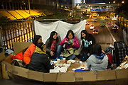A group of Filipino women sit and chat and eat on a fly-over in Hong Kong Central on a Sunday evening. Hong Kong has a huge Filipino population, most of them women working as domestic servants. They meet in public on their days off since none of them have their own private accomodation. 7 million people live on 1,104km square, making it Hong Kong the most vertical city in the world.