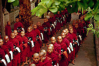 September 1987, Mandalay, Burma (Myanmar) --- Buddhist monks queue up to receive their lunchtime rice at a monastery in Mandalay, Burma. --- Image by © Owen Franken/CORBIS
